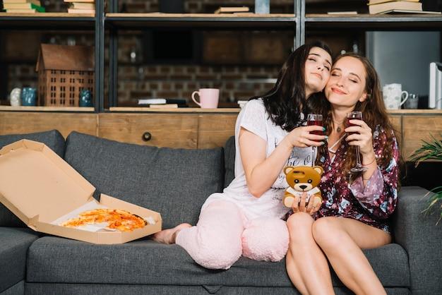 Duas mulheres amigáveis sentado no sofá com bebidas