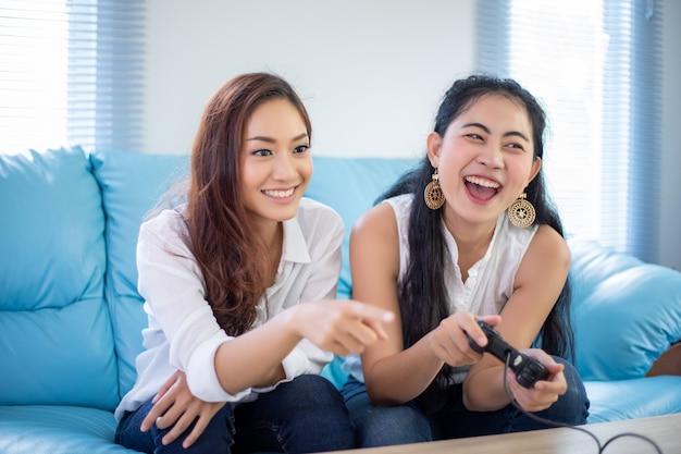 Duas mulheres amigos competitivos jogando videogame e animado feliz alegre em casa