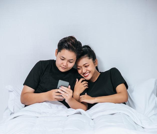 Duas mulheres amorosas dormindo e jogando smartphones.