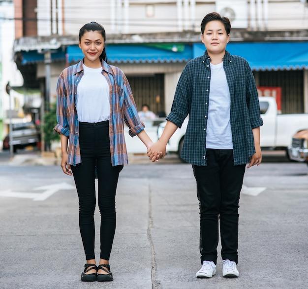 Duas mulheres amorosas em pé e de mãos dadas na rua.