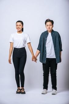 Duas mulheres amorosas em pé e de mãos dadas.