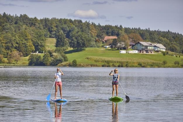 Duas mulheres andando de prancha de stand up paddle no lago smartinsko, na eslovênia