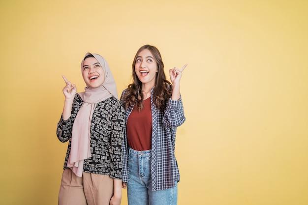 Duas mulheres animadas e rindo lado a lado com gestos de dedo apontando para cima com copyspace