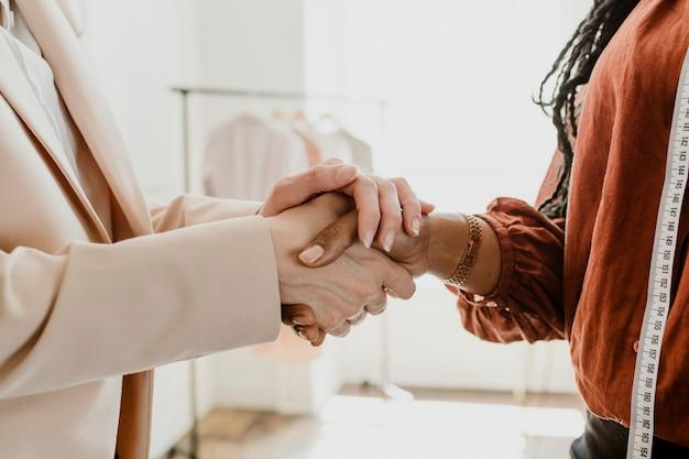 Duas mulheres apertando as mãos em uma boutique