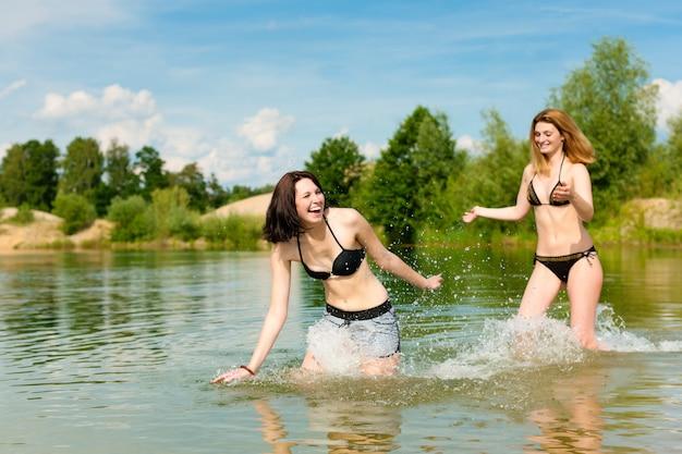 Duas mulheres, aproveitando o dia quente de verão no lago