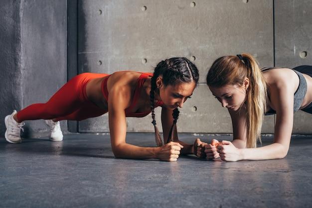 Duas mulheres aptas a fazer exercício de prancha