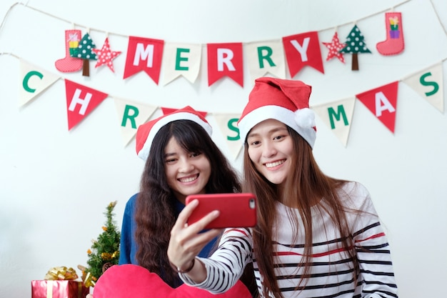 Duas mulheres asiáticas auto-telefone inteligente na festa de natal