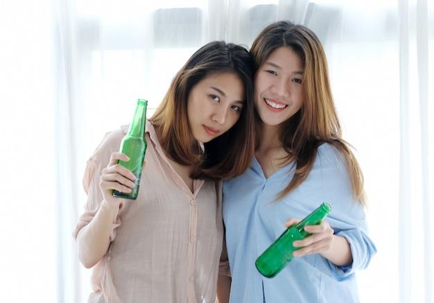 Duas mulheres asiáticas, bebendo cerveja na festa, celebração, casal lgbt, estilo de vida