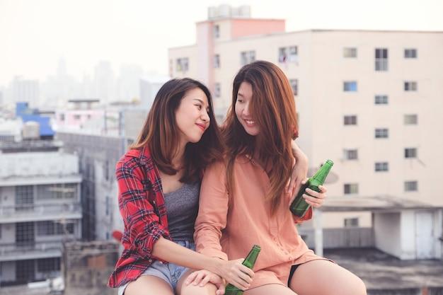 Duas mulheres asiáticas bebendo na festa no terraço, celebração ao ar livre, amizade, casal lgbt