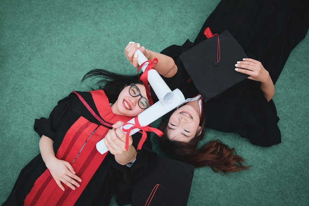 Duas mulheres asiáticas bonitas encontram-se no gramado verde no dia de graduação.