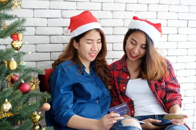 Duas mulheres asiáticas bonitos jovens segurando o tablet e cartão de crédito enquanto fazia compras on-line