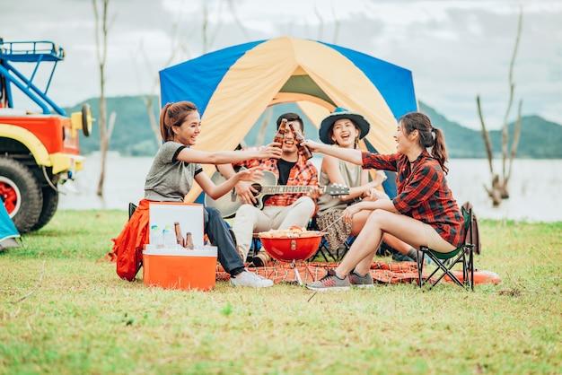 Duas mulheres asiáticas brindando garrafas de cerveja em uma barraca de acampamento de férias