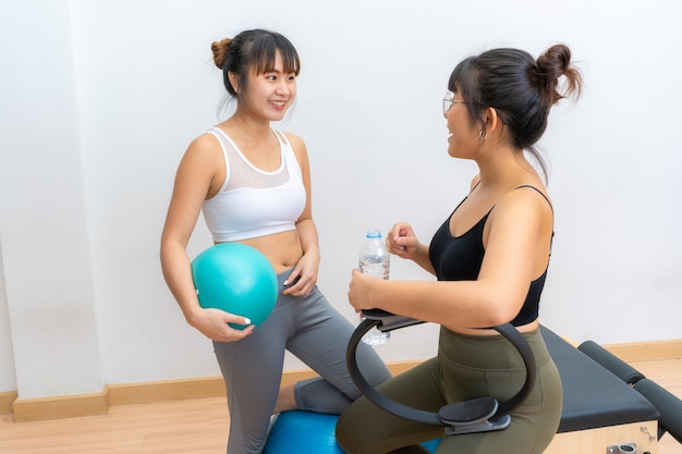 Duas mulheres asiáticas conversando enquanto faziam uma pausa para tomar água durante o exercício de pilates