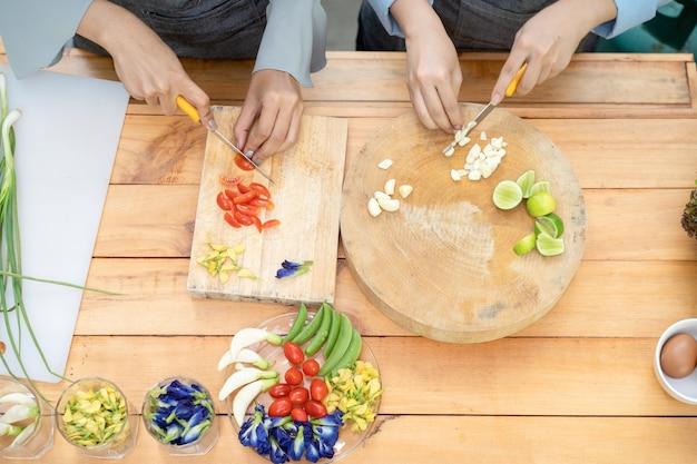 Duas mulheres asiáticas cortam alho e tomate com uma faca na placa de madeira com ervilha-borboleta ervilha-de-lima e ervilhas cebolinhas e ovos naquela área, em seguida, preparando-se para o almoço.