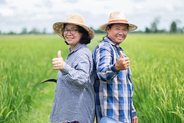 Duas mulheres asiáticas de fazendeiras tailandesas vestem uma camisa azul sorrindo e com o polegar levantado na fazenda verde