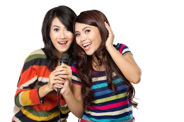 Duas mulheres asiáticas em t-shirt listrada cantando juntos