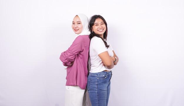 Duas mulheres asiáticas fazendo expressões felizes na superfície branca isolada