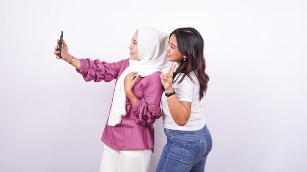 Duas mulheres asiáticas fazendo selfies em uma superfície branca isolada
