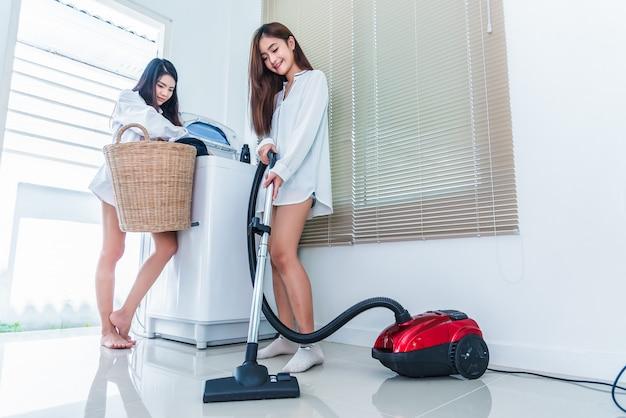 Duas mulheres asiáticas fazendo tarefas domésticas e tarefas na cozinha