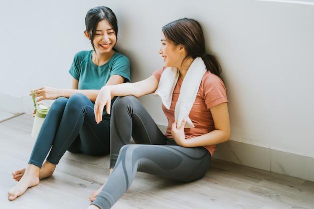 Duas mulheres asiáticas fazendo uma pausa na sessão de ioga