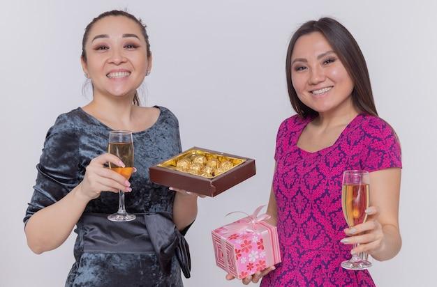 Duas mulheres asiáticas felizes segurando taças de bombons de chocolate com champanhe e presentes comemorando o dia internacional da mulher sorrindo alegremente em pé sobre a parede azul