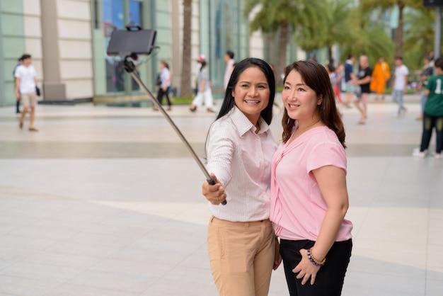 Duas mulheres asiáticas maduras juntas fora do shopping na cidade de bangkok