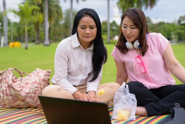 Duas mulheres asiáticas maduras juntos relaxando no parque