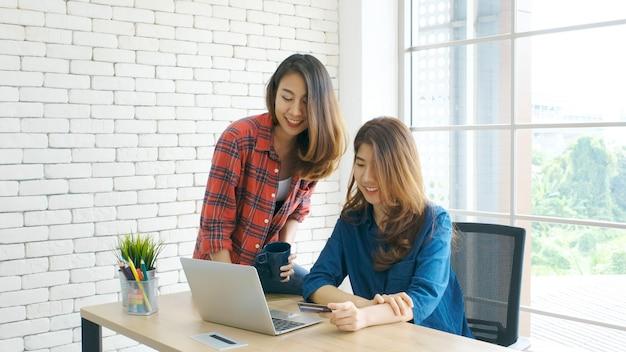 Duas mulheres asiáticas novas que guardam o cartão de crédito e que usam o laptop para comprar na linha.