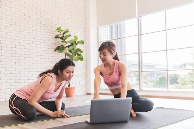 Duas mulheres asiáticas olhando laptop aprendem treinamento de ioga na internet