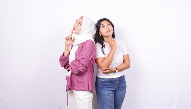 Duas mulheres asiáticas pensando em algo isolado com uma superfície branca