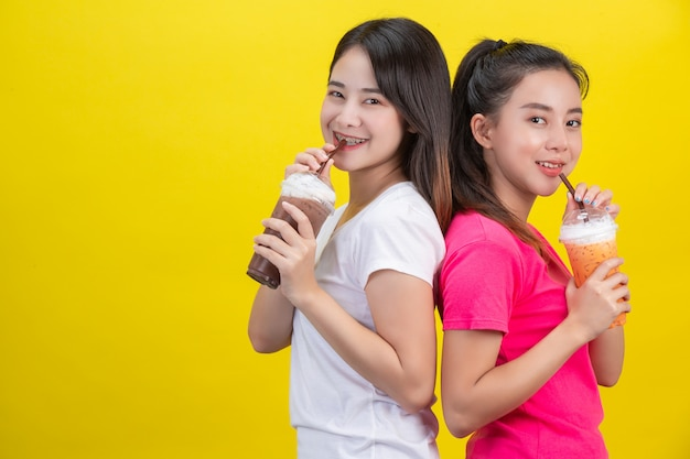 Duas mulheres asiáticas que bebem o chá gelado do leite e o cacau gelado em um amarelo.