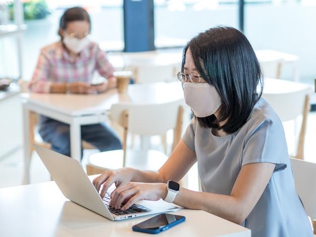 Duas mulheres asiáticas que vestem a máscara protectora e que usam o smartphone e o portátil sentam-se em tabelas separadas para manter o distanciamento social da segurança como o conceito normal novo do estilo de vida.