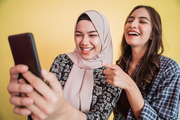 Duas mulheres asiáticas rindo alegremente durante o vídeo usando um smartphone