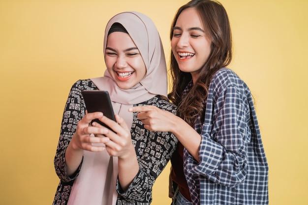 Duas mulheres asiáticas rindo usando um telefone celular enquanto olham para a tela do telefone
