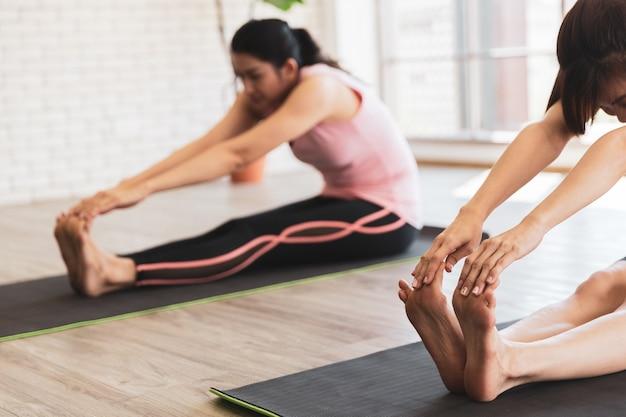 Duas mulheres asiáticas se alongando na aula de ioga