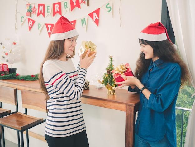 Duas mulheres asiáticas segurando caixa de presente na festa de natal