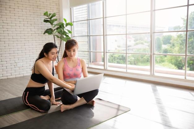 Duas mulheres asiáticas treinam fitness usando um tutorial online