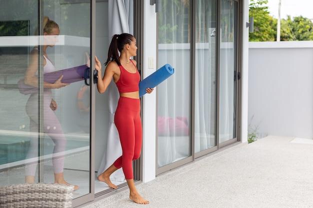 Duas mulheres ativas, asiáticas e brancas, vão praticar ioga ao ar livre em uma vila luxuosa à beira da piscina