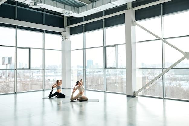 Duas mulheres ativas em forma se exercitando em colchonetes com os braços atrás da cabeça durante o treinamento físico em um grande centro de lazer contemporâneo