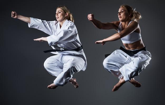 Duas mulheres atletas treinando caratê usando ferramentas esportivas
