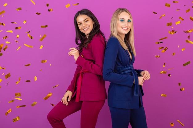 Duas mulheres atraentes comemorando o ano novo na parede violeta em elegantes ternos coloridos de cor roxa e azul, amigos se divertindo juntos, tendência da moda, clima de festa confete dourado