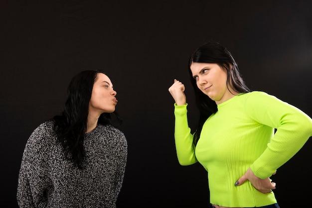 Duas mulheres atraentes discutindo e mostrando os punhos e a língua uma à outra