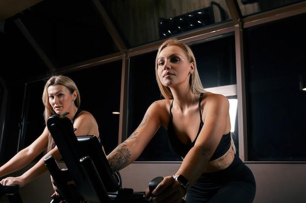 Duas mulheres atraentes e desportivas andando de bicicleta ergométrica durante o treinamento de ciclismo no ginásio