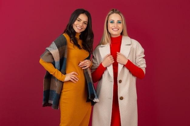 Duas mulheres atraentes e elegantes sorridentes com vestido de moda outono inverno e casaco posando isolado na parede vermelha