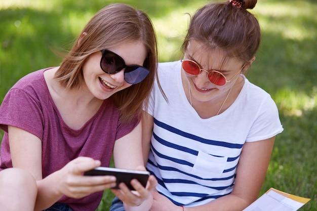 Duas mulheres atraentes em óculos de sol da moda têm expressões felizes, vestidas com camisetas casuais, assistem a vídeos engraçados no telefone inteligente, usam internet sem fio, posam no parque contra um fundo de grama verde.