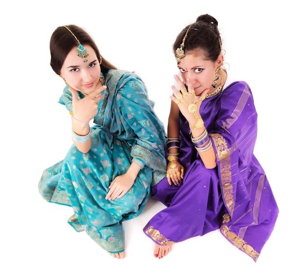 Duas mulheres atraentes em pé com roupas tradicionais indianas em azul e roxo