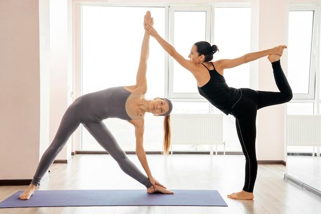 Duas mulheres atraentes equilibrando e praticando ioga em um estúdio leve. bem estar bem estar