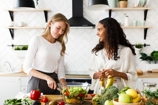 Duas mulheres atraentes na cozinha estão cozinhando o café da manhã saudável de frutas e legumes