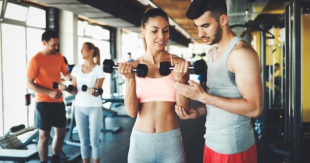 Duas mulheres atraentes se exercitando com personal trainers na academia