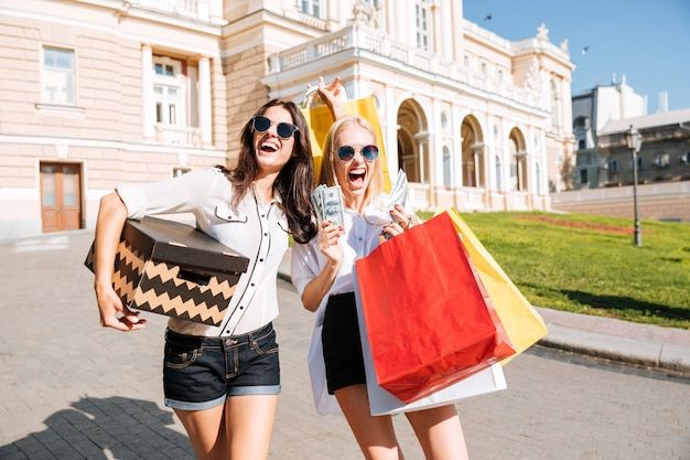 Duas mulheres atraentes segurando sacolas de compras e sorrindo ao ar livre